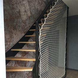 Rampe d'escalier avec cadre en acier et filet de sécurité verticale